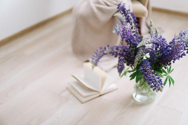 花瓶の夏の構成で花と本の紫色のルピナスの花束とインテリアの家の装飾