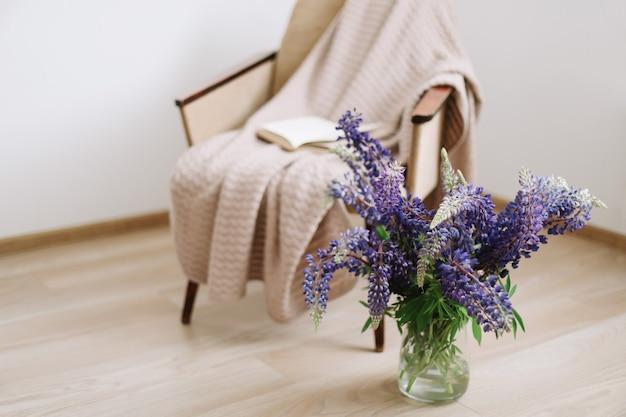花瓶に紫色のルピナスの花と本の花束とインテリアの家の装飾