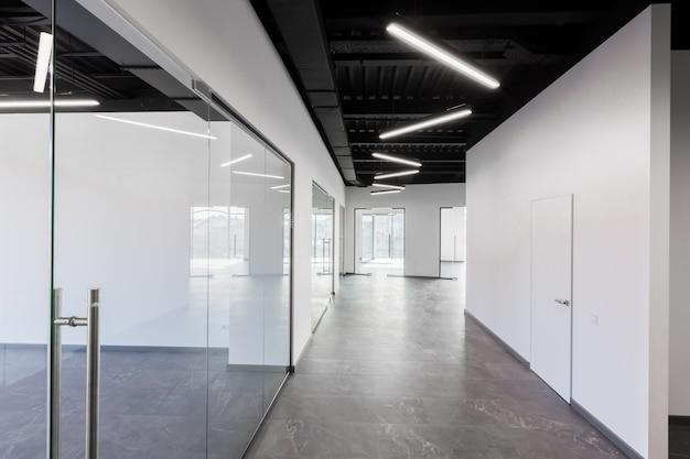 탁 트인 창문과 가구가없는 유리문이있는 넓은 사무실 내부