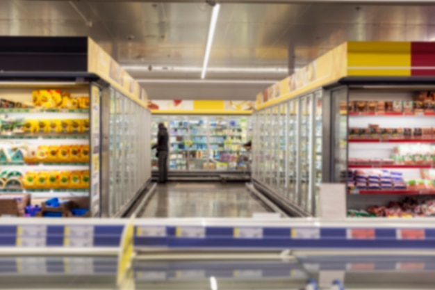 Interior of a large supermarket with glass display cases with refrigerated products.