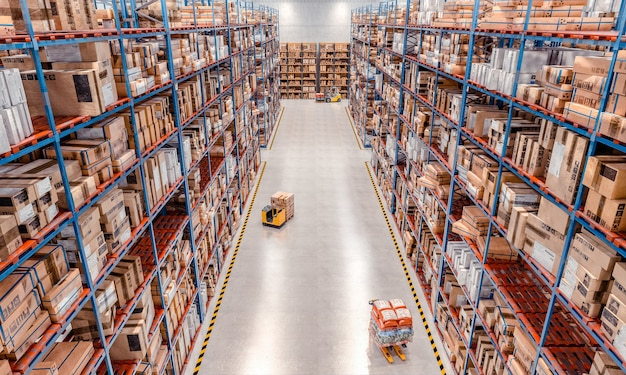 Interior of a large warehouse with very high shelves and lifting equipment in action