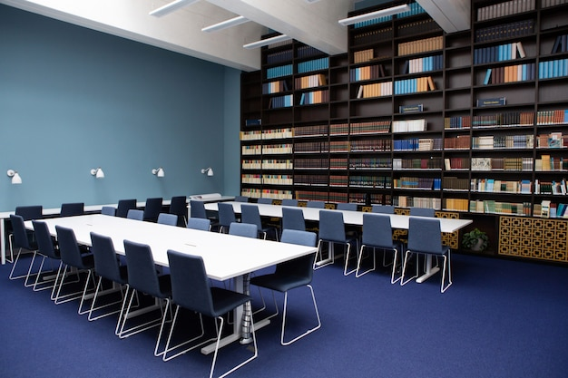 The interior of the library, blue and brown colors. bookcases with books, white tables.