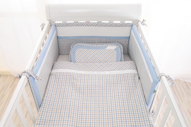 Interior of light cozy baby room with crib and bedding