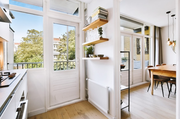 Interior of light kitchen and dining room with balcony doors in contemporary apartment at daytime