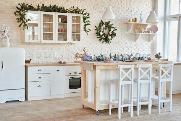 Внутренняя светлая кухня с рождественским декором и деревом. белая кухня в классическом стиле. рождество на кухне. яркая кухня в белых тонах с рождеством.