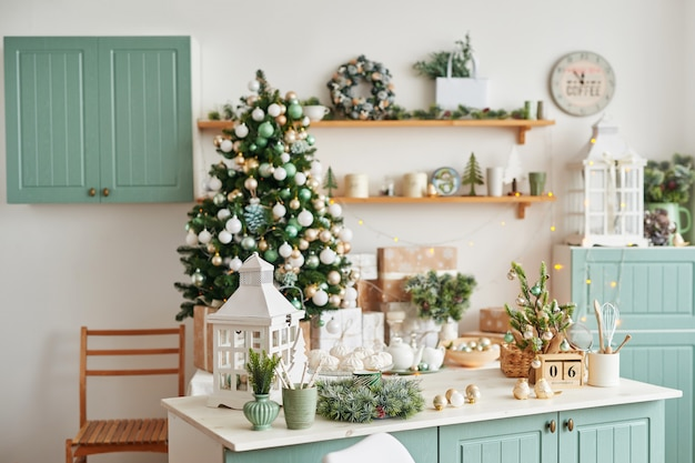 Interior light kitchen with christmas decor and tree. turquoise-colored kitchen in classic style .