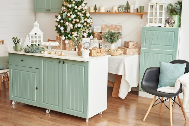 Interior light kitchen with christmas decor and tree. turquoise-colored kitchen in classic style