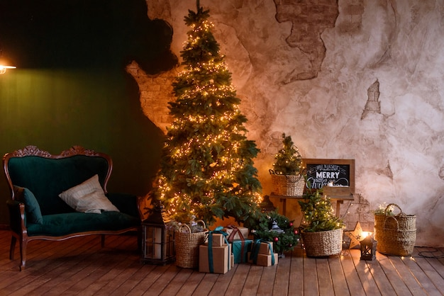 The interior of the living room in the christmas style with a large fir-tree and сhristmas gifts