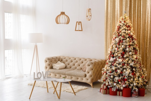 Interior living room with a sofa, table, floor lamp and panoramic window. christmas tree