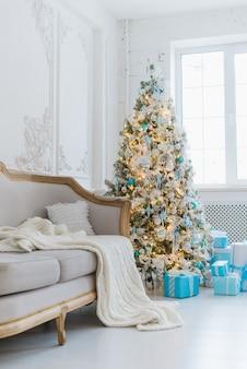 インテリア高級ホームリビングルーム飾られたクリスマスツリーとギフト、毛布で覆われたソファ