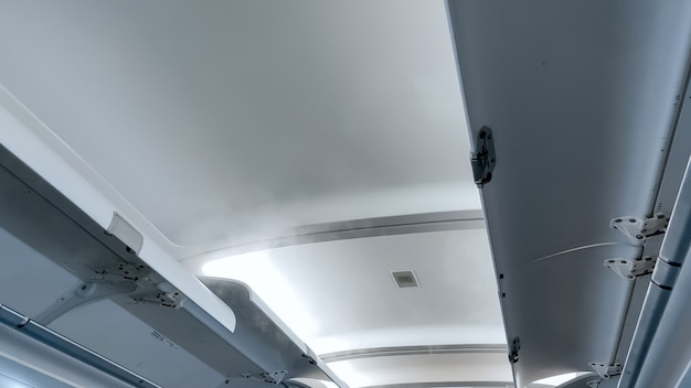 Interior of modern airplane with open shelves for luggage.