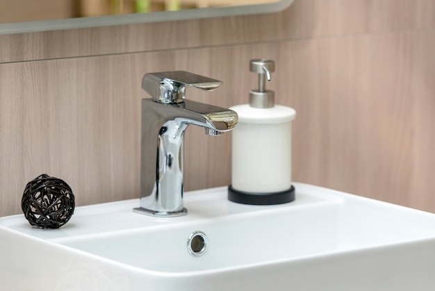 Interior of modern bathroom with white sink and faucet, close-up sink