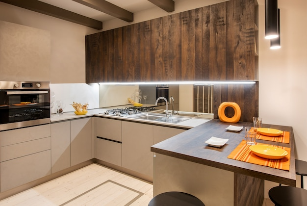 Interior of modern fitted kitchen with orange accents and neutral beige coloured cabinets with recessed lighting