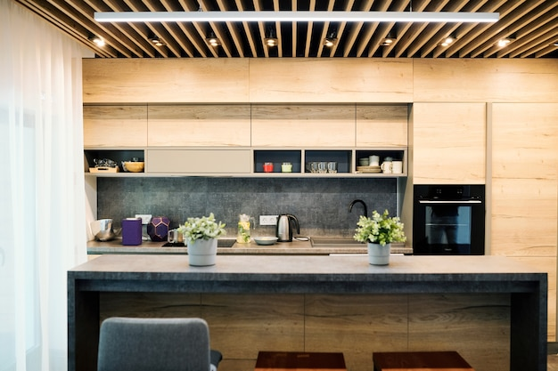 Interior of modern kitchen that is large, comfortable and of stylish design with table, kitchenware, oven and cabinets