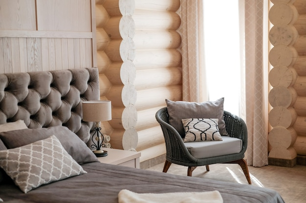 Interior of  modern light wooden room with high window with curtain comfortable chair at sunny day