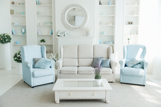 The interior of the modern living room with a white sofa, blue armchairs and a bookshelf