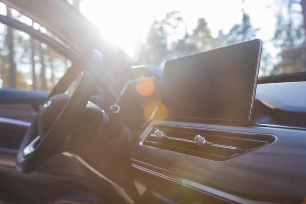 Interior of modern luxury car in sunshine monitor airduct and steering wheel on premium car side