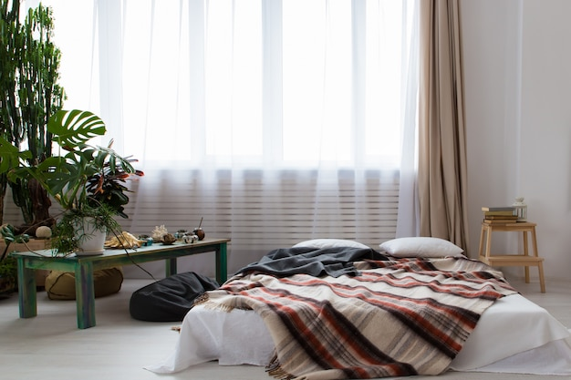 Interior of a modern studio apartment with lots of plants and a bed on the floor