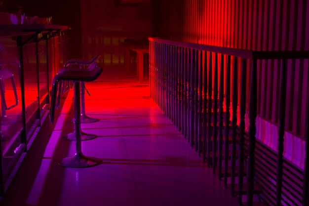 Interior of a nightclub with colorful red and purple lighting and a line of stylish bar stool along a reflective bar counter with a railing behind