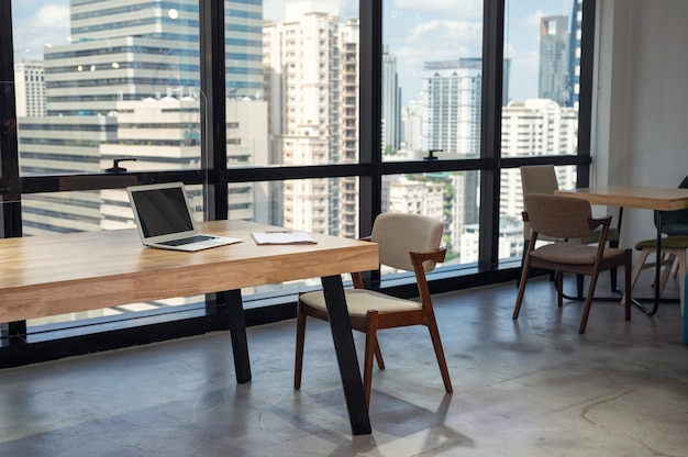 Interior of nobody modern office with laptop, clipboard on wooden desk and chair in busuness district