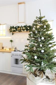 Интерьер новогодней светлой кухни, украшенной елкой и гирляндами