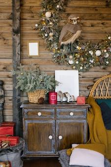 Интерьер комнаты загородного дома с рождественским венком, старинным комодом и декором на рождество и новый год.