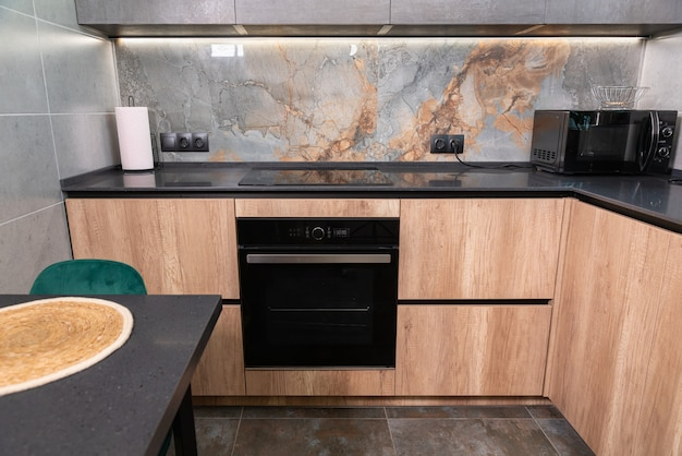Интерьер встроенной кухни с деревянными шкафами и встроенной бытовой техникой с серыми каменными столешницами и мраморным фартуком, просматриваемый за подходящим столом.