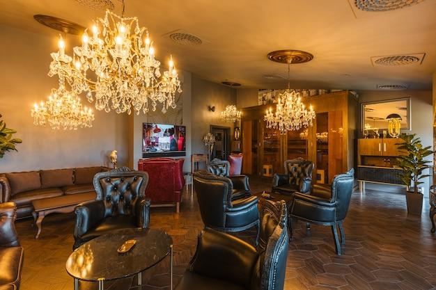 Интерьер роскошной сигарной комнаты с огромными люстрами и кожаными креслами.
