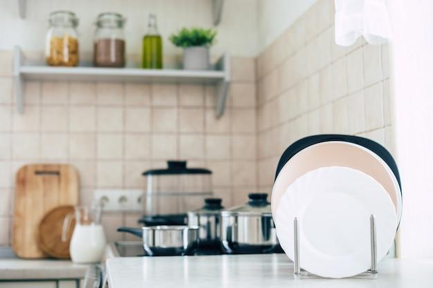 テーブルの上に皿とストーブの上に鍋があるモダンで美しいライトキッチンのインテリア
