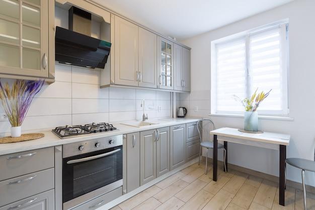 小さなスマートなアパートのモダンなベージュとグレーのキッチンのインテリア