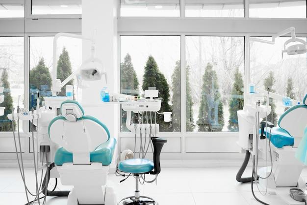 새로운 치과 의자가있는 현대 치과 의사 사무실의 인테리어