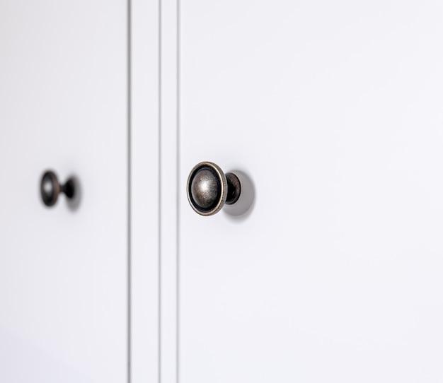 Интерьер современного жилого дома: деталь черных дверных ручек кухонного ящика.