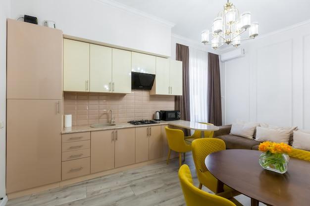 小さなアパートのモダンでスタイリッシュなキッチンのインテリア、家具付き、パステルカラー、黄色とベージュ