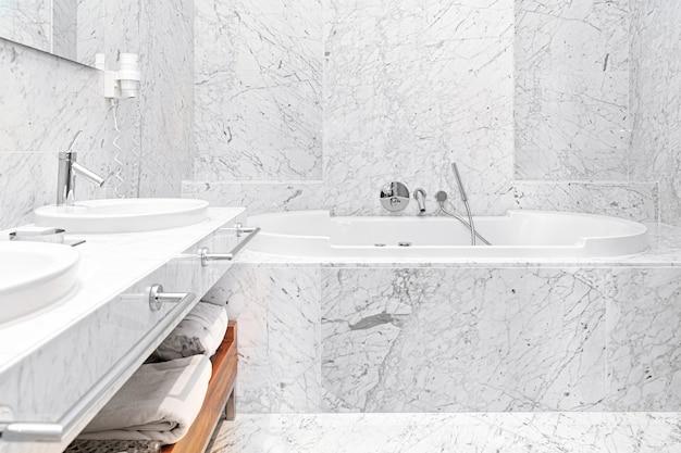 バスタブとタオル付きのモダンな白い大理石のホテルのバスルームのインテリア