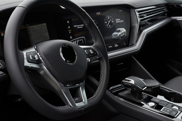 名門のモダンな黒い車のインテリア。革製の快適なシートとアクセサリー、ステアリングホイール