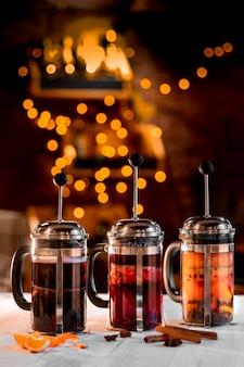 ガーランドの黄金のボケライト、異なる種類のお茶とフレンチプレスでクリスマスに装飾されたレストランのインテリア