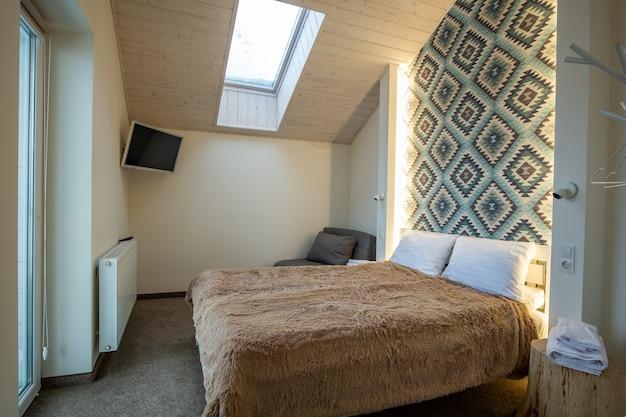 큰 더블 침대에 신선한 린넨이 있는 다락방 바닥에 있는 넓은 호텔 침실의 내부입니다. 현대적인 집에 있는 아늑한 현대식 맨사드 룸입니다.