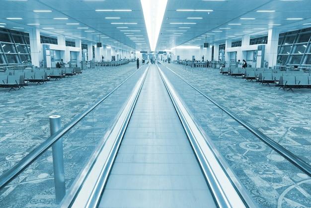 플랫 에스컬레이터가 있는 공항 홀 내부. 블루 컬러 이미지