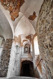 Интерьер старинного средневекового здания со сводом с белой потрескавшейся штукатуркой и кирпичной стеной