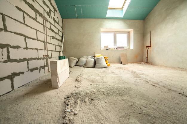 むき出しの壁と天井が建設中のアパートの部屋のインテリア。