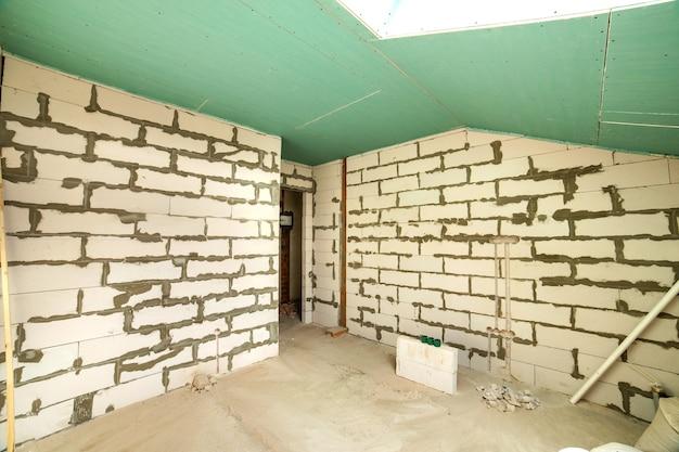 맨 손으로 벽과 천장이 건설중인 아파트 방의 내부.