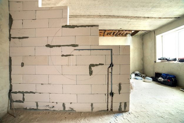 Интерьер квартиры с голыми стенами и строящимся потолком.