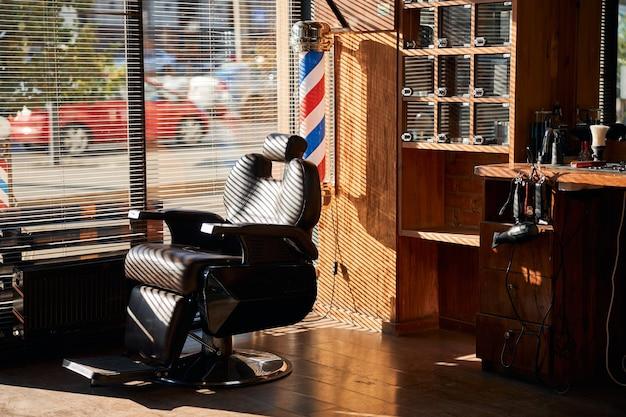 Интерьер парикмахерской с парикмахерским креслом и парикмахерскими инструментами