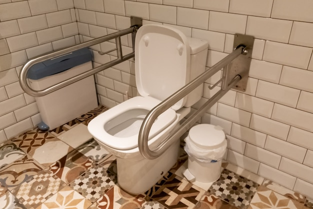 Интерьер ванной комнаты с перилами для инвалидов или пожилых людей.
