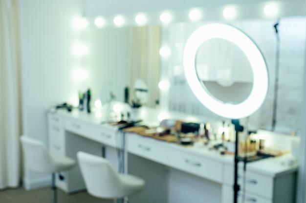 ぼやけた光のスタジオの美しさのインテリアは、大きな発光鏡とテーブルの背景を持つサロンを構成しています。