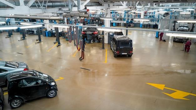Интерьер автосервиса с поднятыми над полом автомобилями