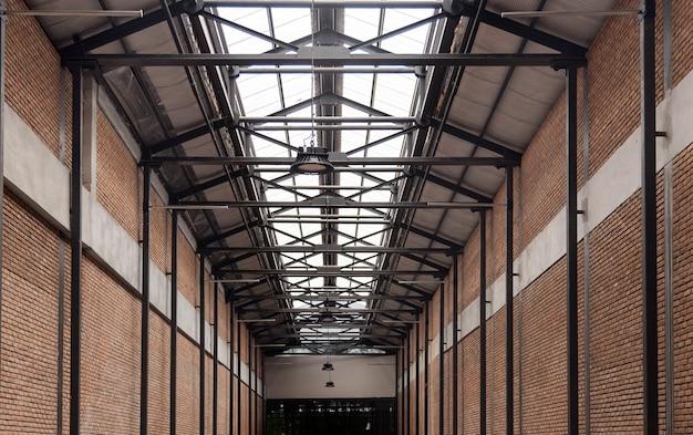Интерьер цементной стены с высокой крышей солнечного света внутрь фабрики