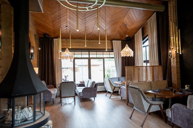 Интерьер стильного и уютного ресторана со столиками и мягкими диванами вдоль окон и стен.