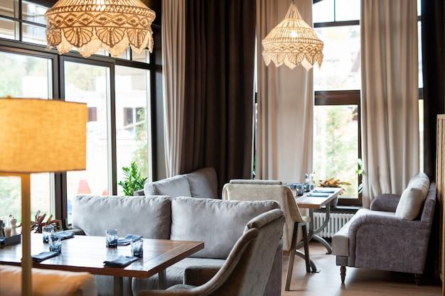 Интерьер уютного и роскошного ресторана с мягкими серыми бархатными диванами и деревянными столами.