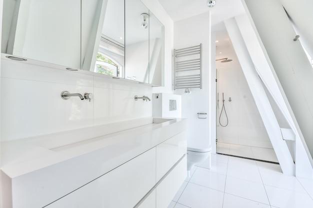 Интерьер современной ванной комнаты с белой керамической раковиной и душем в стиле минимализма